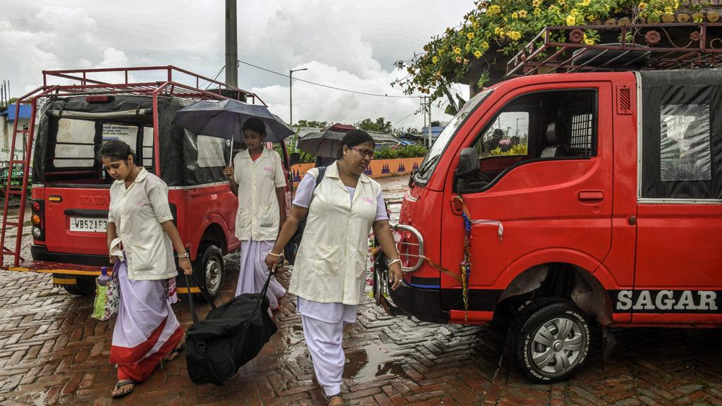 Women walk past two vans.