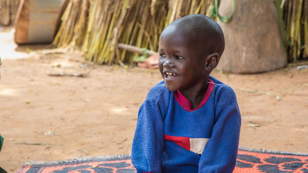 With his sight restored, Muzi sits with a smile on his face in his village in Nigeria