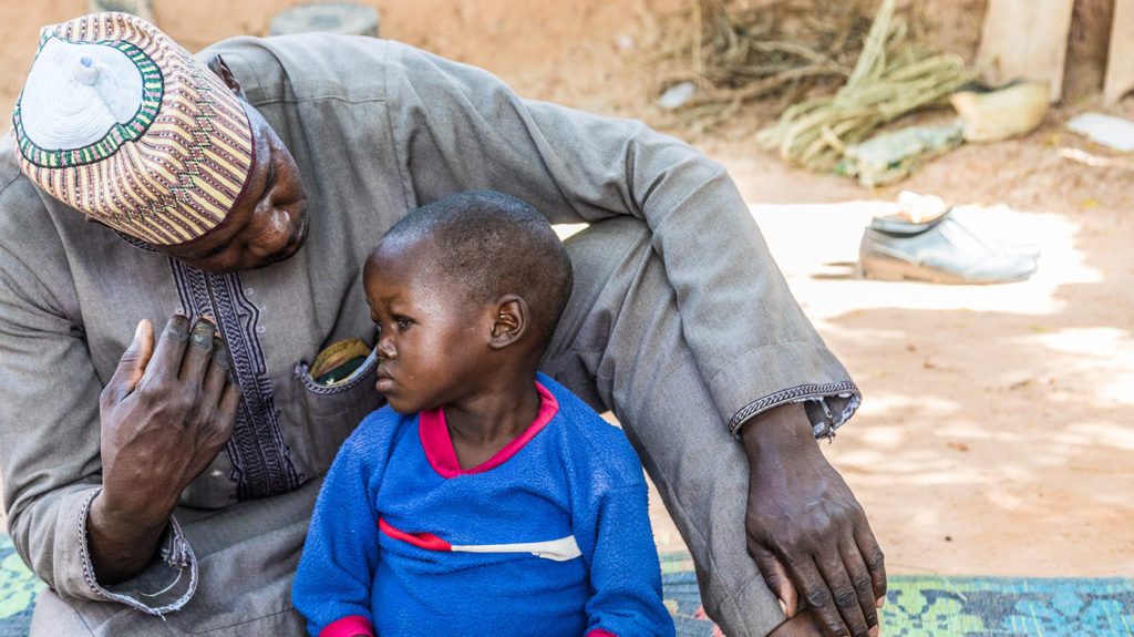 Muzi and his protective Father sat outside in his village in Sokoto, Nigeria.