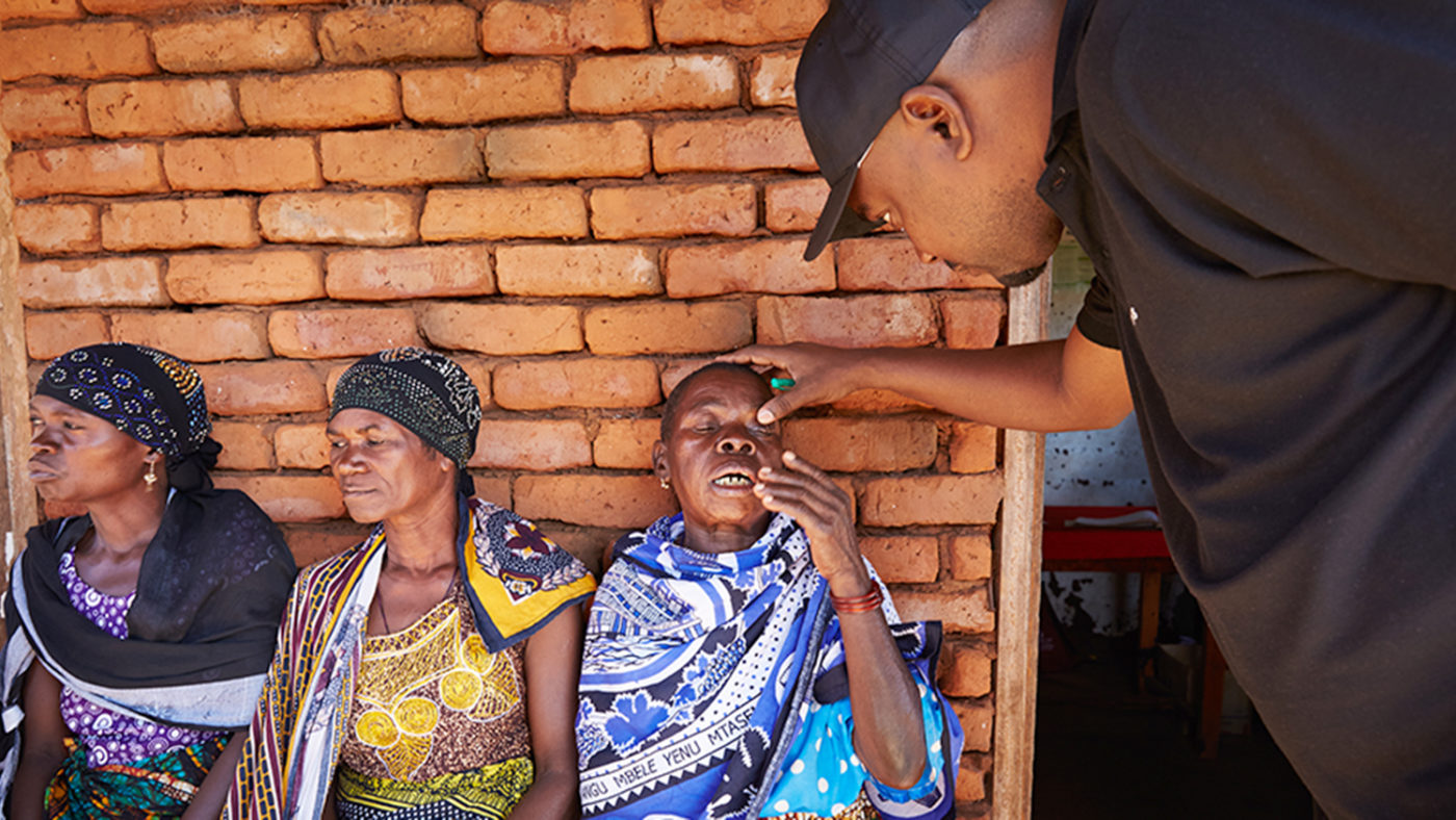 Mwita examines a woman's eyes.