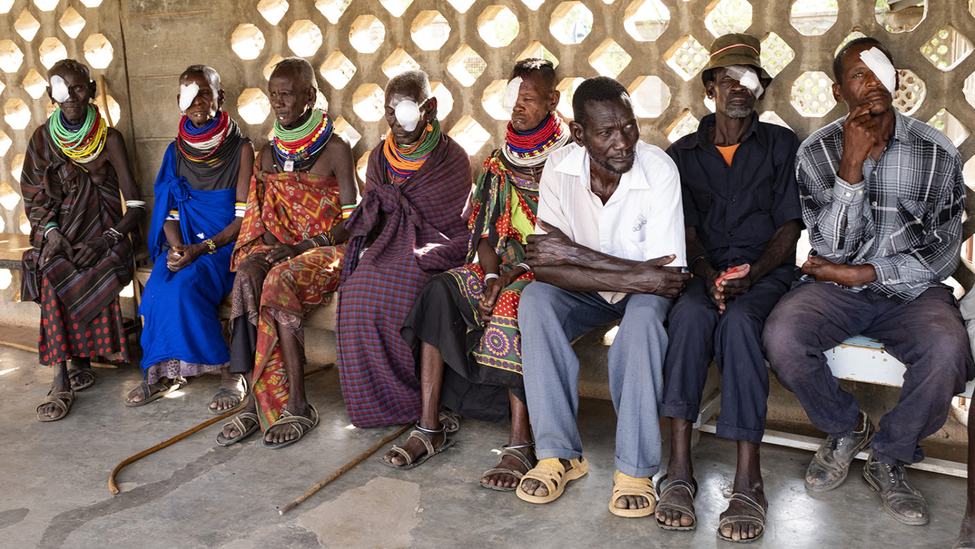 People with patches over one eye sit at a health clinic.