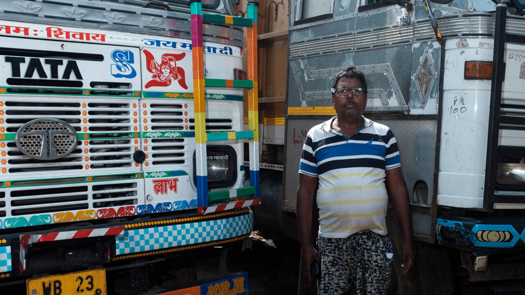 A man standing infront of a colourful truck.