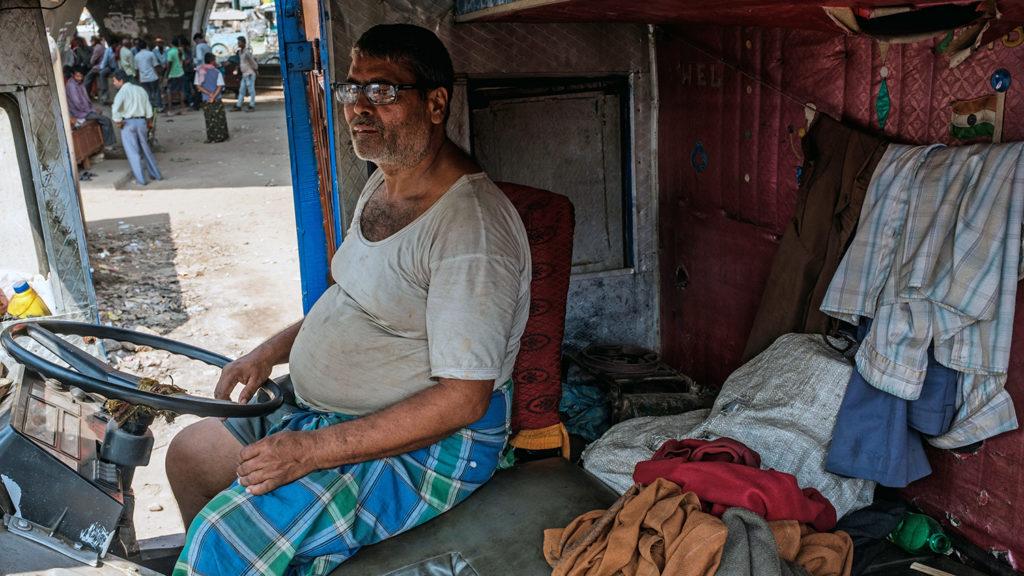 A man sits inside a truck.