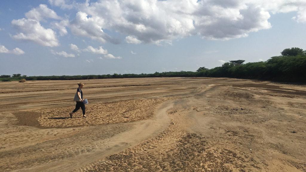 A women walks across a vast dried up river bed.