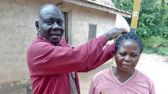 Emmanuel Nyamkeen measures a woman's height to determine how much medication to give her.