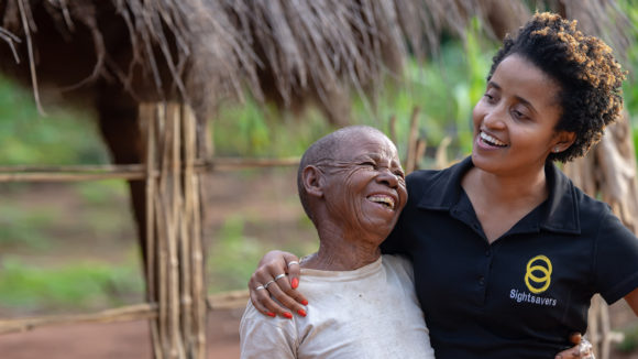 Mercia celebrates with a trachoma surgery patient after her bandages have been removed.
