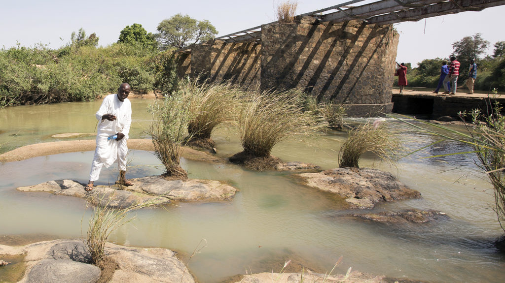 A man in Nigeria stands on a rock to fish from a river.