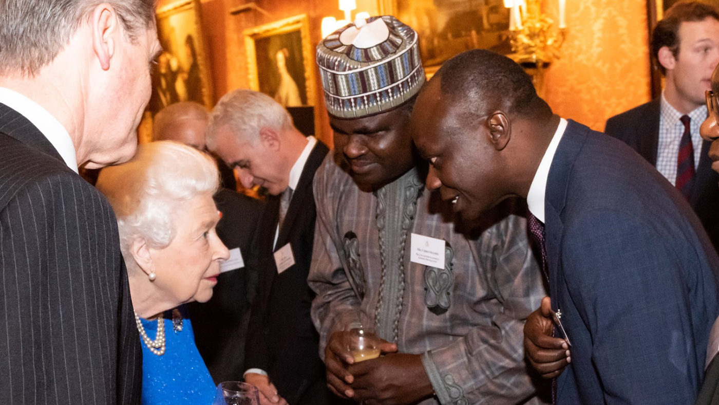 The Queen greets Sunday Isiyaku and other guests at the Buckingham Palace event.