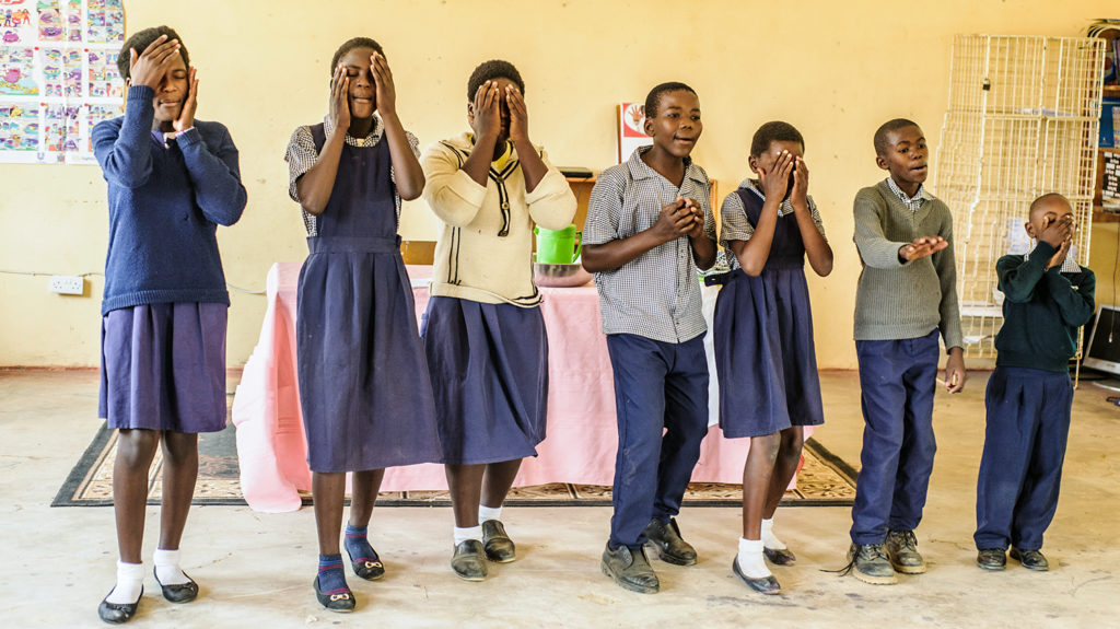 School children in Zambia act out a play showing how they wash their faces.