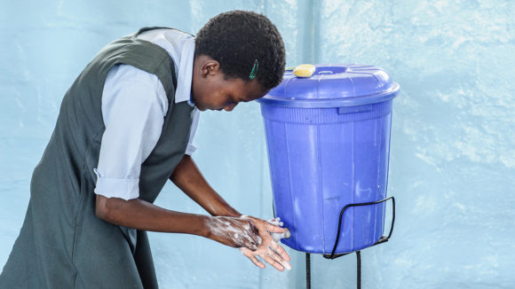 A school student washes her hands using water from a large plastic bucket.