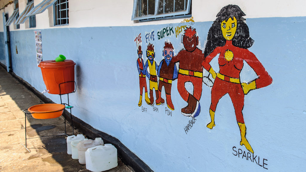A mural on a school wall showing five superhero characters.
