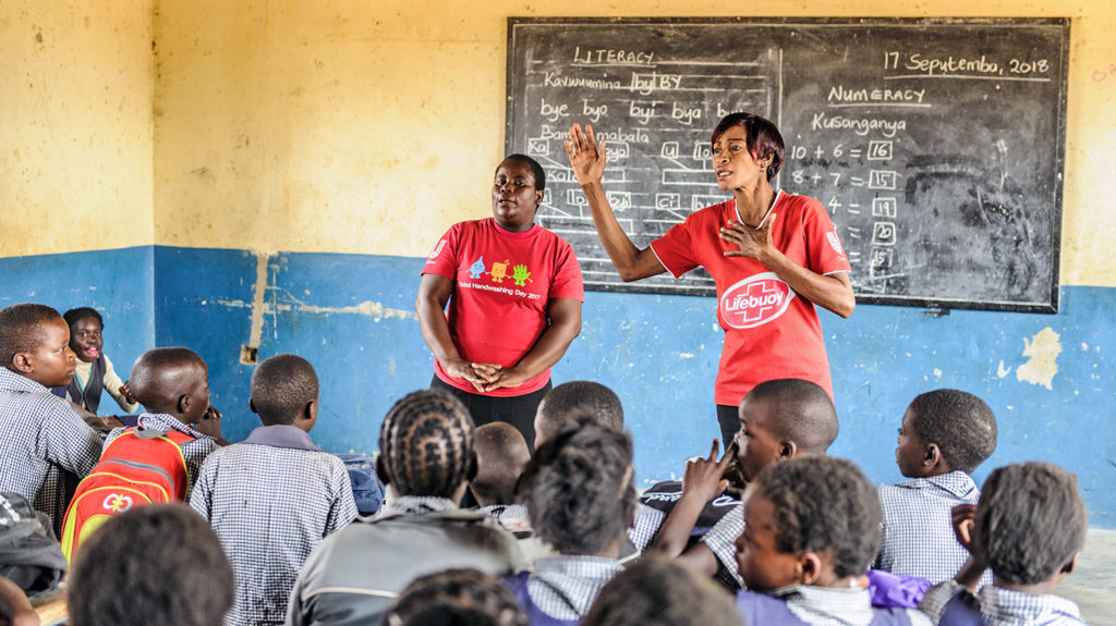 Two teachers stand in front of their class in Zambia.
