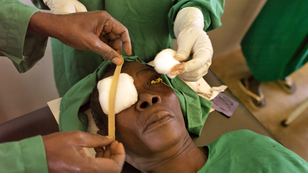 A woman has dressings applied to her eyes after trachoma surgery.