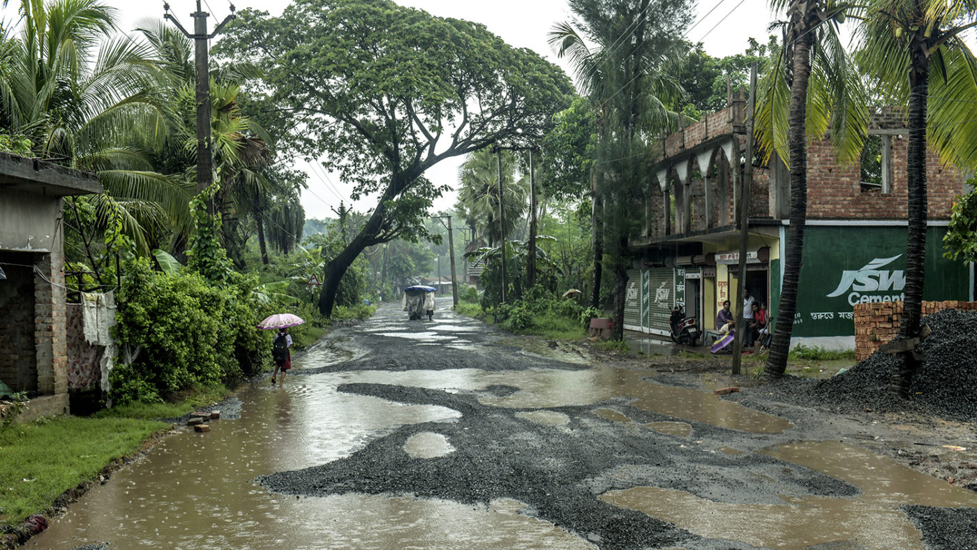 A road with many large puddles of water.