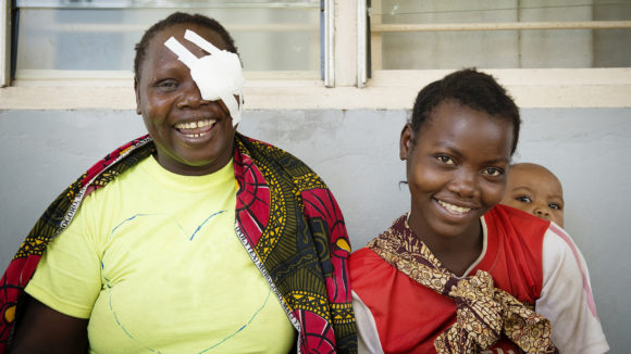 A woman with a bandaged eye and a girl smiling