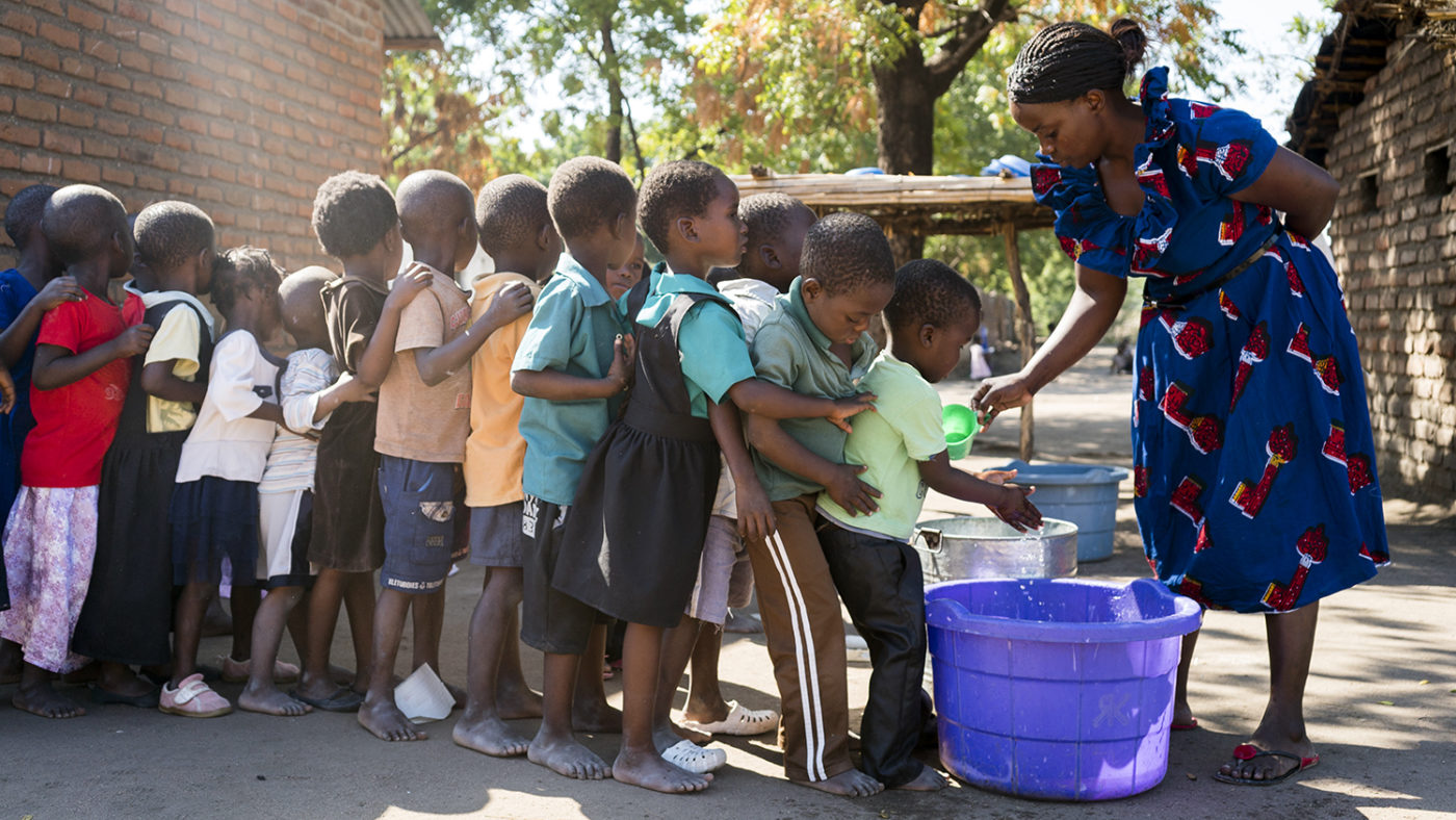 Children line up to wash their hands outside in a bucket.
