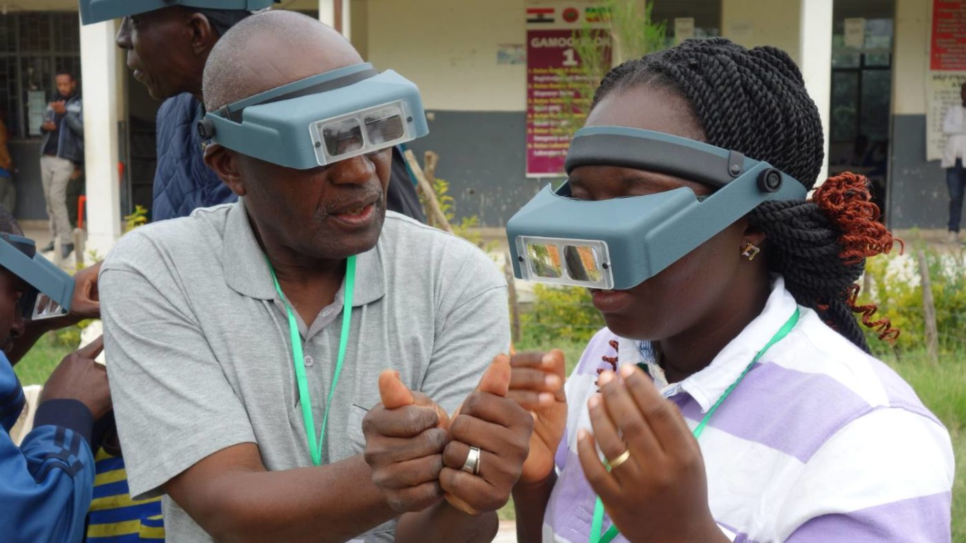 A male Tropical Data trainer shows female trainee how to identify what trachoma follicles would look like by using small, circular, red stickers with five white dots on their thumbs.