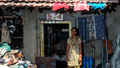 A women stands outside her home.