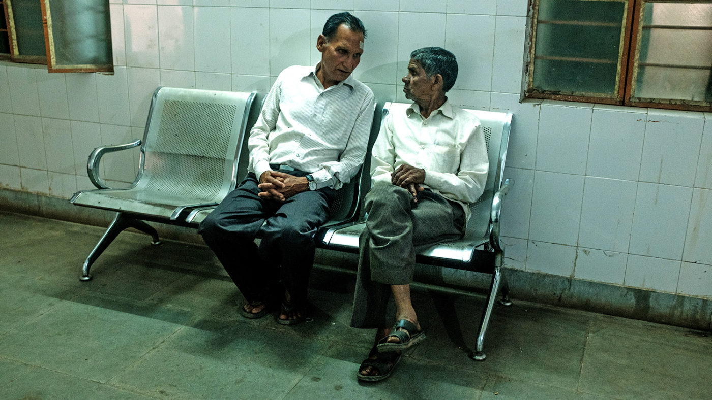 Two men sit in a hospital waiting area, talking to each other.