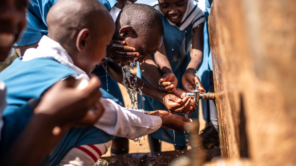 School children in Africa use a tap to wash their hands and faces.