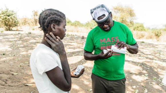 A man distributes treatment to a trachoma patient in Zimbabwe.