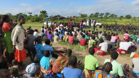 Many people sit outside on the ground in Malawi.