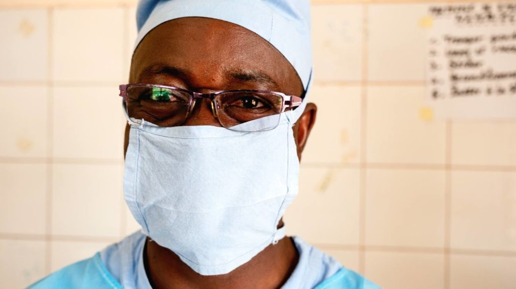 A trachoma surgeon stands for a portrait wearing his surgical scrubs and mask.