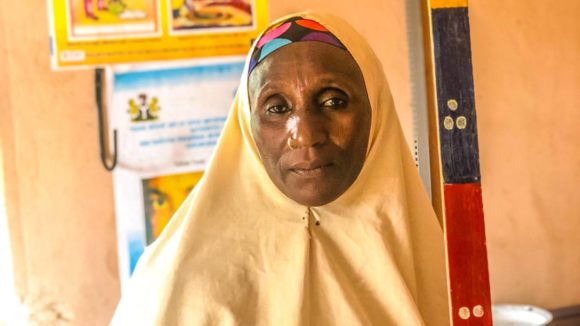 A community volunteer from Nigeria stands for a portrait holding a dose pole, which is used to measure patients' height and determine how much medication they require.