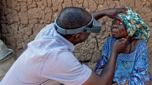 Trachoma surgeon checks the eyes of a patient for signs of trachoma outside her home in Benin.