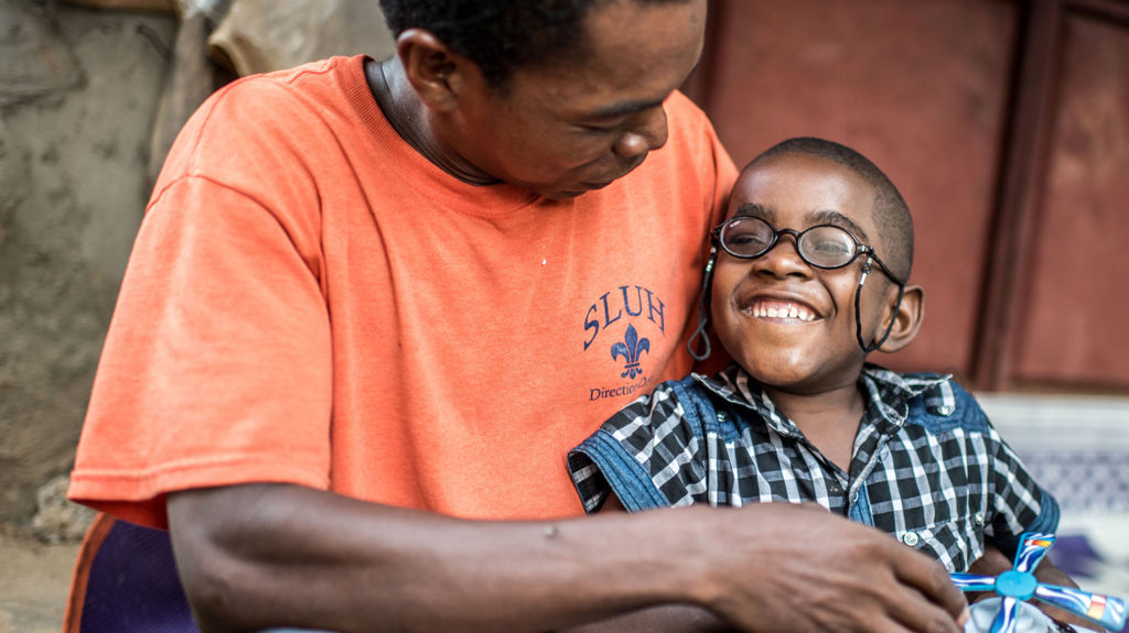 Saidi from Zanzibar smiles with his family member after his cataract operation.