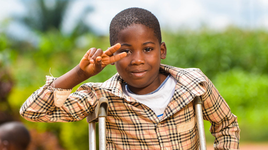 Zambo makes a V for Victory sign with his fingers at school in Cameroon.