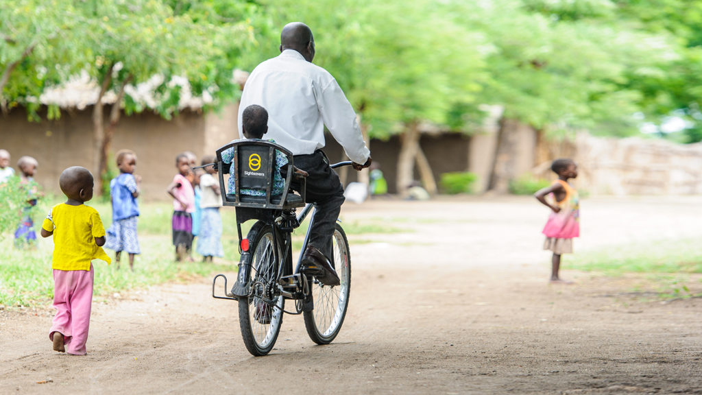 A man rides a bike with a child on the back.