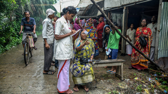 A woman has her eyes checked by an eye health worker in an outdoor screening camp in India.