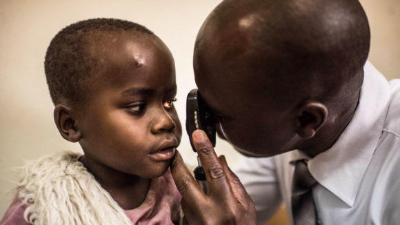 A doctor checks a young child's eyes.