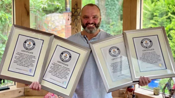Lee Spencer holding his Guinness World Record certificates.