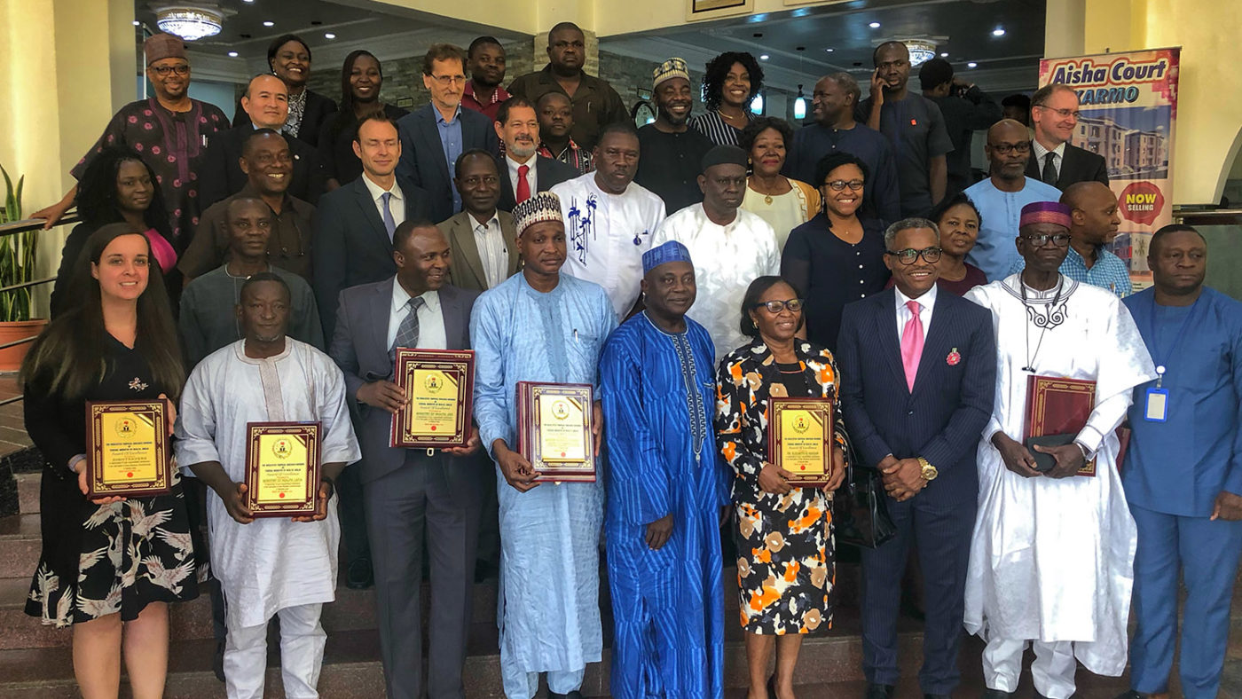 A large group of people stand with their awards for tackling river blindness in Nigeria.