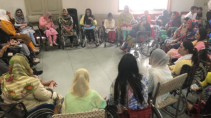 A large group of people, most of whom are wheelchair users, sit together in a circle.
