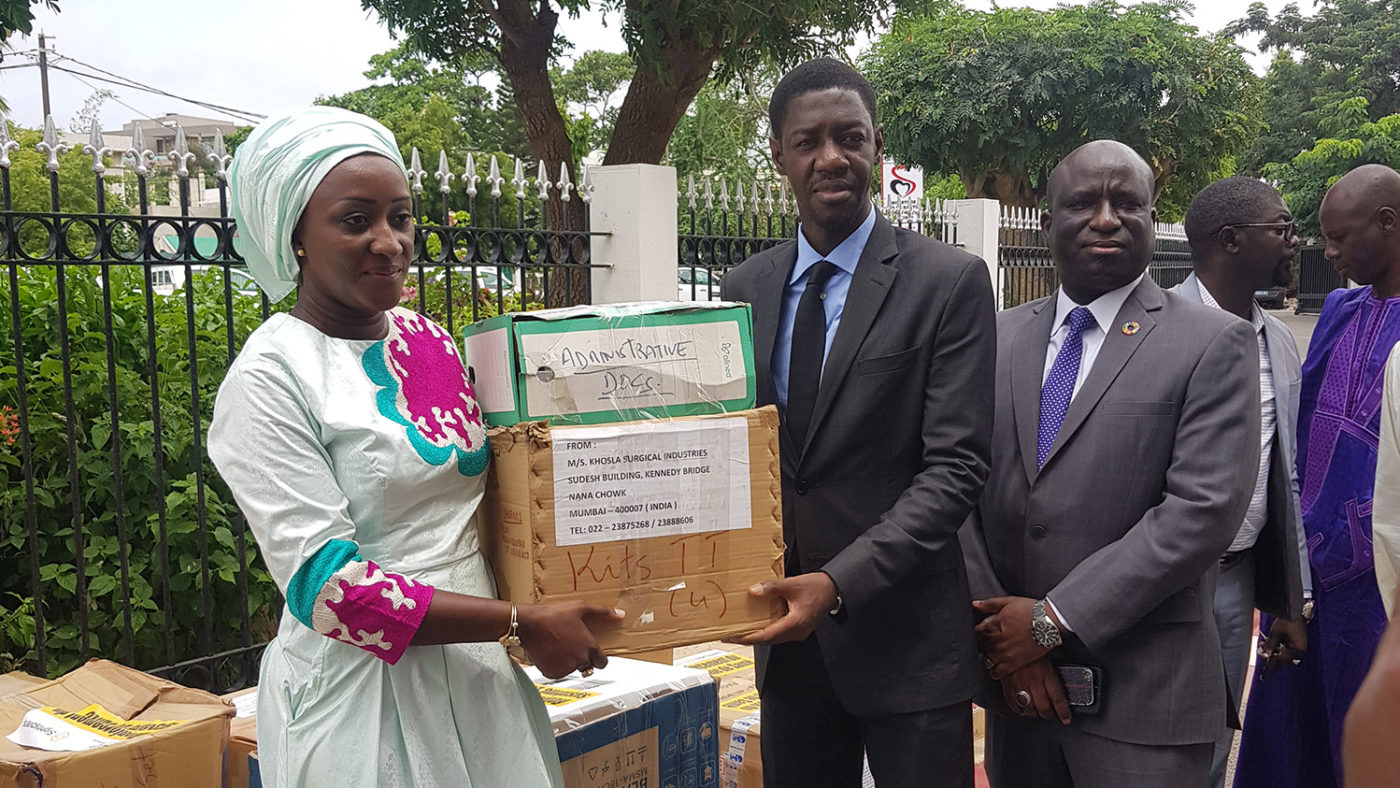 A man and woman stand with a box of donated medicines.