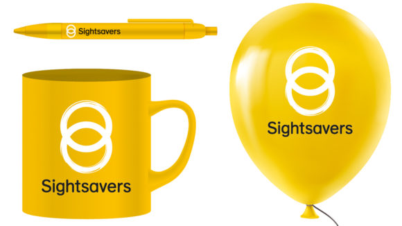 Examples of Sightsavers-branded items: a pen, a mug and a balloon, all yellow with the Sightsavers logo.