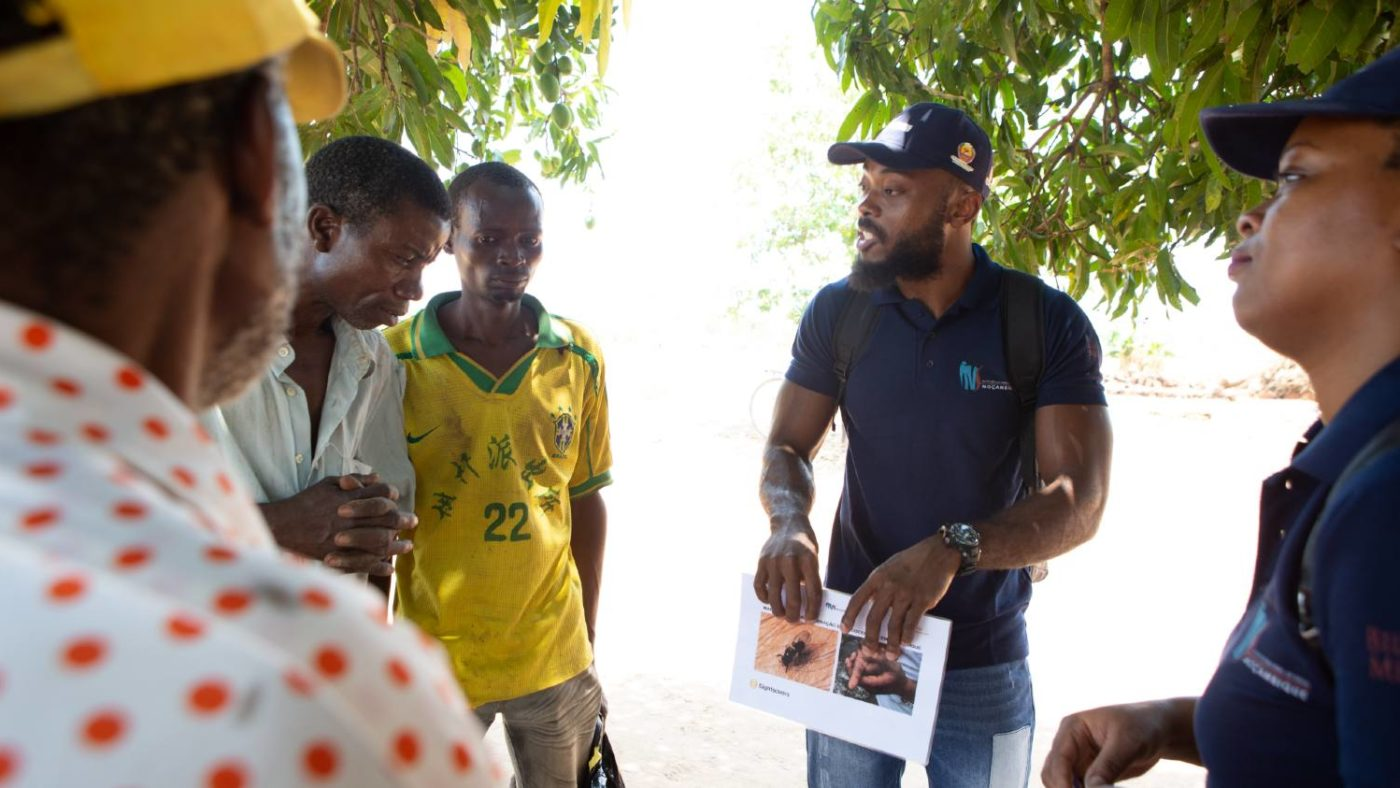 A community volunteer explaining about river blindness to community members.