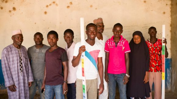 A group of female and male community volunteers stand for a portrait holding dose poles.