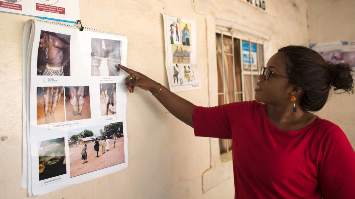 A woman points at a poster which shows the side affects of lymphatic filariasis