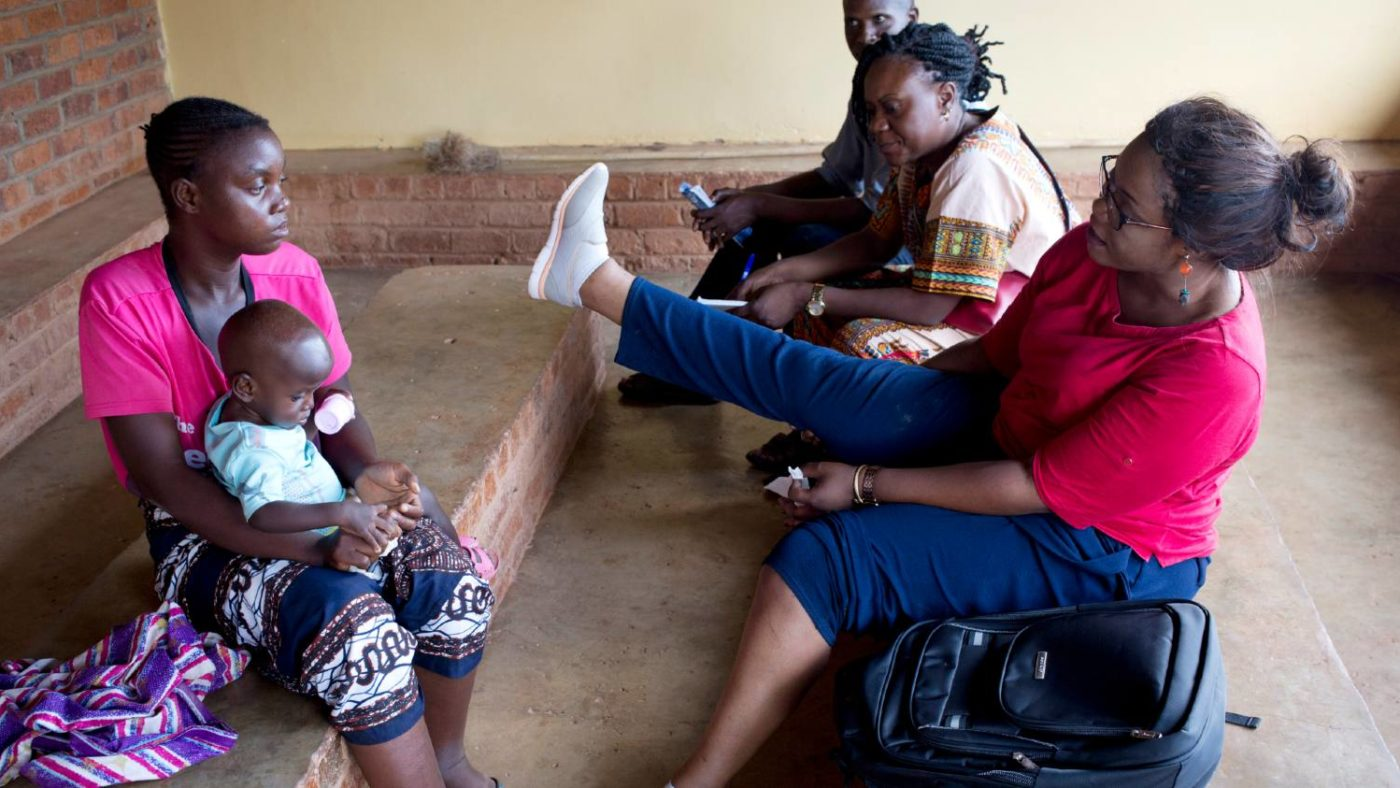 A doctor shows a patient who has lymphatic filariasis how to reduce swelling by putting her leg up.