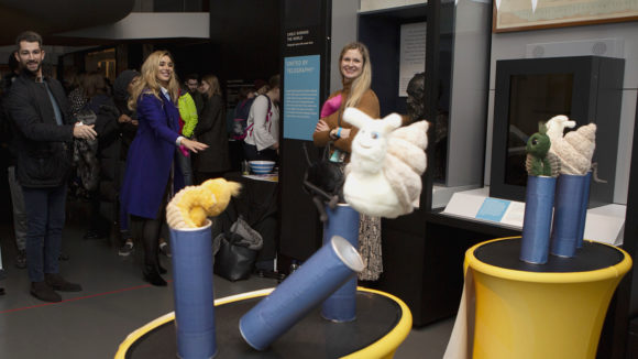 Science Museum Lates attendees play a coconut-shy styled game where participants throw bean bags at plush toys.