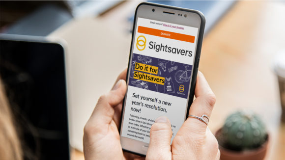A close-up of someone using a smartphone to read a Sightsavers email.