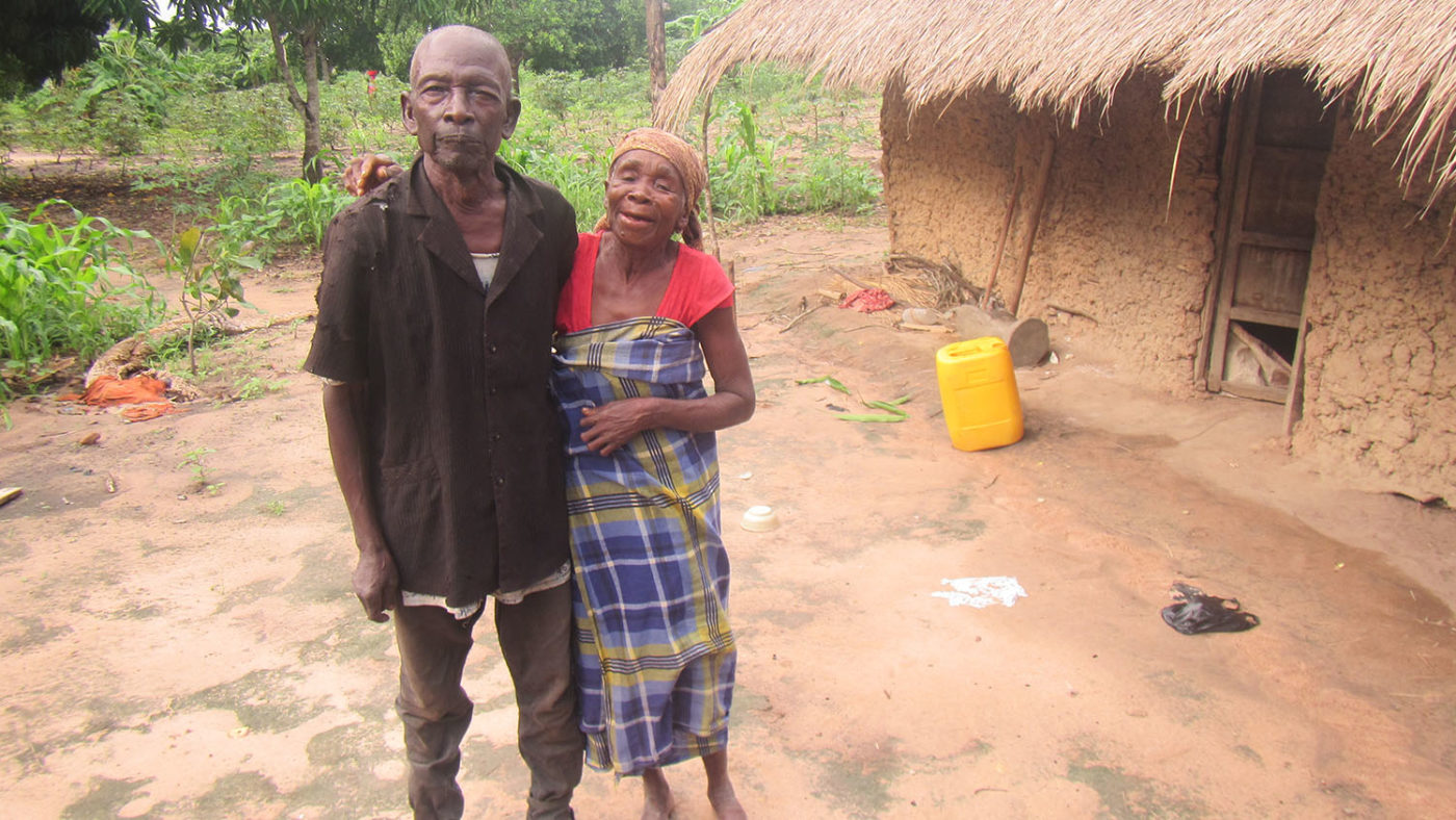 A couple stand together outside their home.