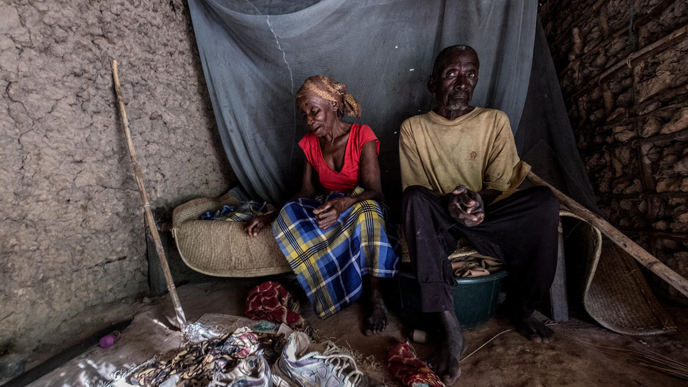 A man and woman sit in the darkness in their home.