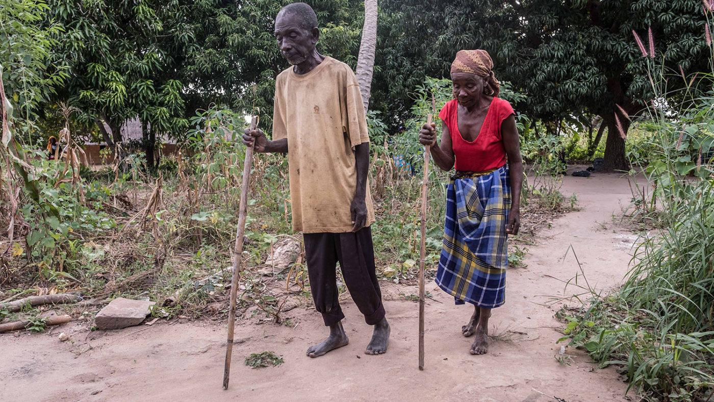 A man and woman use sticks to navigate.