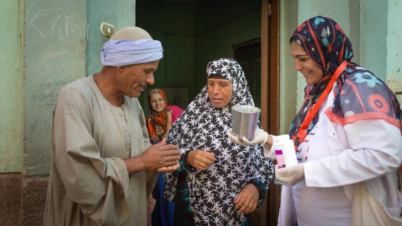 A community volunteer distributes treatment to a couple.