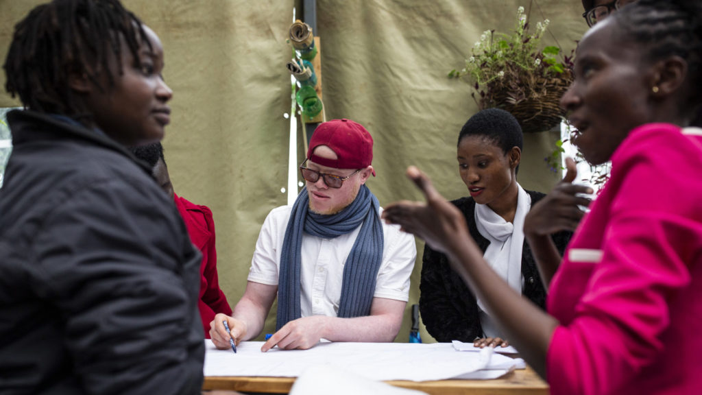 Four people with disabilities, including a man with albinism, sit together around a table working.